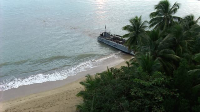 high angle down moving back and forth along a long stretch of coastline.  two landing craft infantry or lci ships land on the beach, dumping out soldiers, jeeps, and trucks.  an amphibious assault.  supposed to be the bay of pigs, but could be used for ww - military land vehicle stock videos & royalty-free footage
