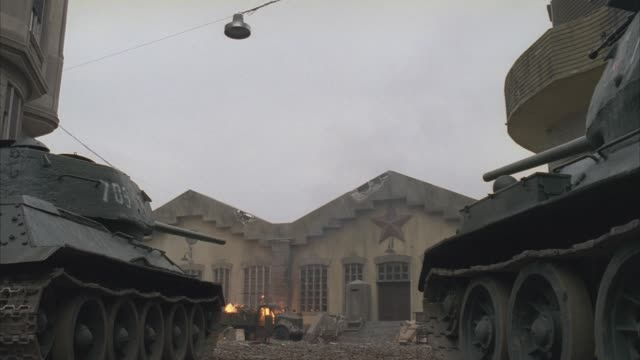 WIDE ANGLE OF TWO TANKS, PROBABLY FROM THE GERMAN NAZI ARMY, SHOOTING AT A BUILDING WITH A SOVIET STAR. COULD BE A WAREHOUSE, BARRACKS, MILITARY BASE OR MILITARY CAMP.  LOOKS LIKE WWII BATTLE OR URBAN BATTLEFIELD. SEE THE END OF THE CLIP IN 4068-003.