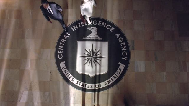 "CLOSE ANGLE PULL BACK TO HIGH ANGLE STRAIGHT DOWN OF ""CENTRAL INTELLIGENCE AGENCY, UNITED STATES OF AMERICA"" EMBLEM, SEAL, OR INSIGNIA ON LOBBY GROUND. THE EMBLEM'S SYMBOLS ARE A RIGHT FACING EAGLE HEAD, SIXTEEN POINT COMPASS STAR OR COMPASS ROSE, AND SHI"