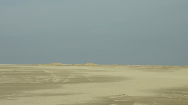 WIDE ANGLE OF A DESERT OR BEACH AS A TANK RISES UP FROM THE HORIZON AND DRIVE RIGHT IN FRONT OF THE CAMERA.  PROBABLY A RUSSIAN TANK PARTAKING IN THE SOVIET INVASION OF AFGHANISTAN. BATTLEFIELDS, BATTLES, MILITARY VEHICLES, SOLDIERS.