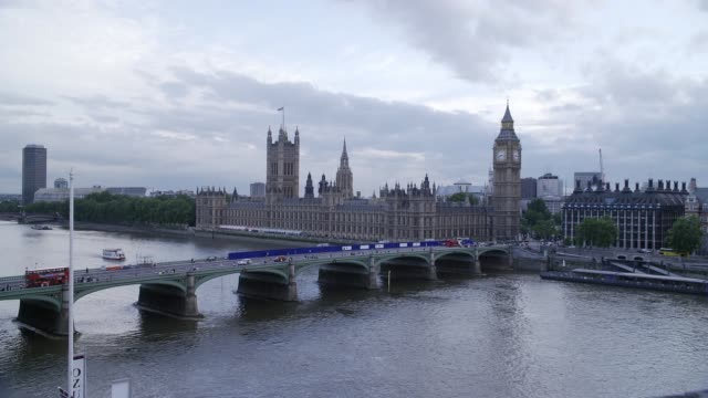 high angle down of westminster bridge spanning thames river in london. parliament buildings and big ben clock tower in bg. government buildings. cloudy. people walk across bridge. cars driving. water. ferries and boats in water. landmarks. - ビッグベン点の映像素材/bロール