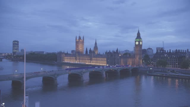 high angle down of westminster bridge spanning thames river in london. parliament buildings and big ben clock tower in bg. government buildings. cloudy. people walk across bridge. cars driving. water. lights. landmarks. - ビッグベン点の映像素材/bロール