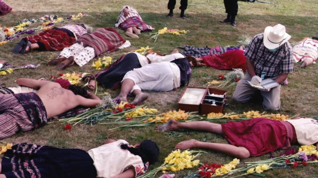pan right to left of people lying on grass in semi-circle around fire pit. could be mass-suicide, religious or cult ritual. field or meadow. could be dead bodies or corpses. men, women, children. flowers. could be villagers or natives. police officers, cr - indigenous culture stock videos & royalty-free footage