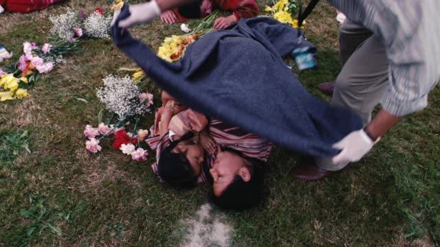 medium angle of man, could be coroner, placing blanket over dead woman and her daughter, girl or child. people lying on grass in semi-circle around smoking fire pit. could be mass-suicide, religious or cult ritual. field or meadow. could be dead bodies or - indigenous culture stock videos & royalty-free footage