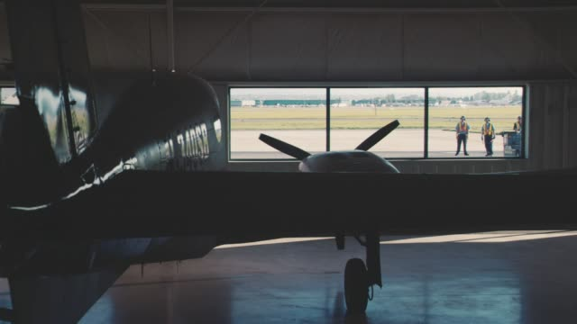 medium angle of small airplane parked inside hangar with glass window. additional hangars visible through window in bg. technicians visible outside window. limo drives by window. - airplane hangar stock videos & royalty-free footage