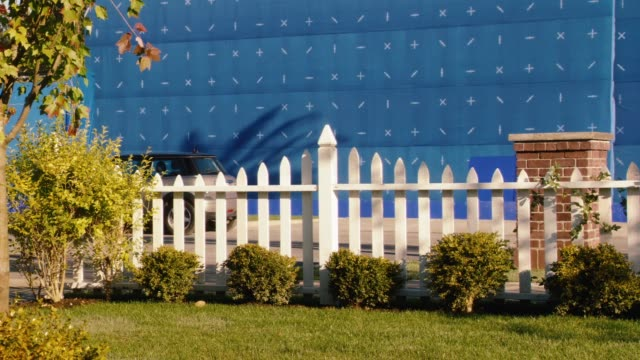 vídeos de stock, filmes e b-roll de medium angle of residential area or neighborhood with white picket fence and cars parked on curb. blue screen bg. neighborhood begins to shake. earthquake. - cerca