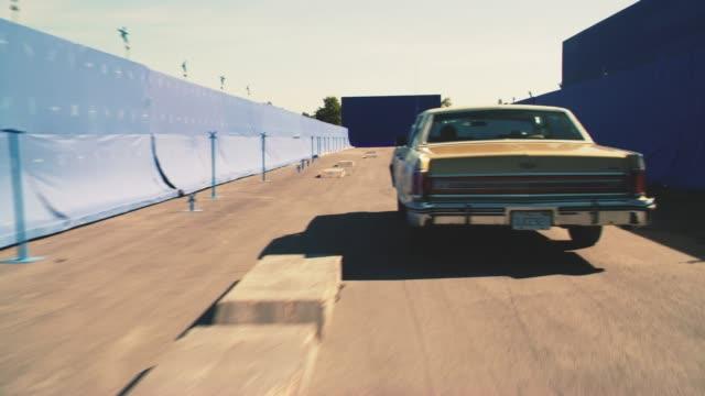 vídeos de stock e filmes b-roll de wide angle of car driving down blue screen street. car swerves around obstacles. - imagem em movimento