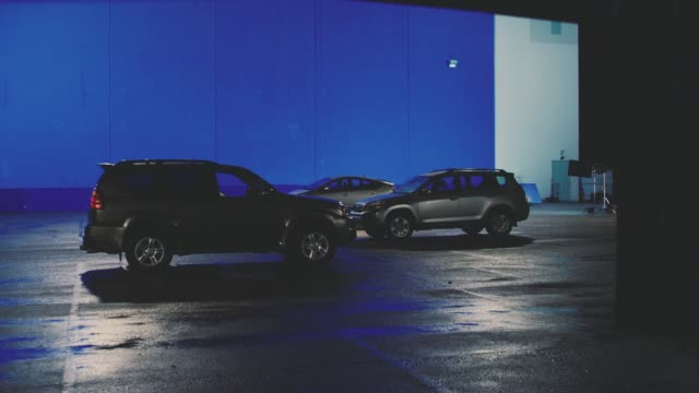 wide angle of three cars in parking lot. head and tail lights flash. blue screen. - headlight stock videos & royalty-free footage