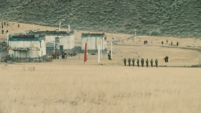 wide angle of military or army base in rural area or mountains. buddhist prayer flags on guard towers. soldiers and truck. dry grass fields. - military base stock videos & royalty-free footage