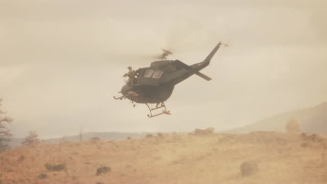 wide angle of army or military suvs or hummers parked on dry, arid hill in desert area. hovering military helicopter kicks up dust. could be military base or camp. - military helicopter stock videos & royalty-free footage