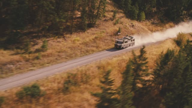 aerial of rv driving on dirt or mountain road surrounded by trees and forest. mountains visible in bg. could be national park. - camper van stock videos & royalty-free footage