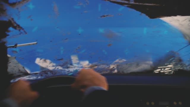 close angle of man's hands on steering wheel with blue screen in bg. driving. debris, mud, paper, and rubble begins to hit car. boxes. could be disaster. - chroma key stock videos & royalty-free footage