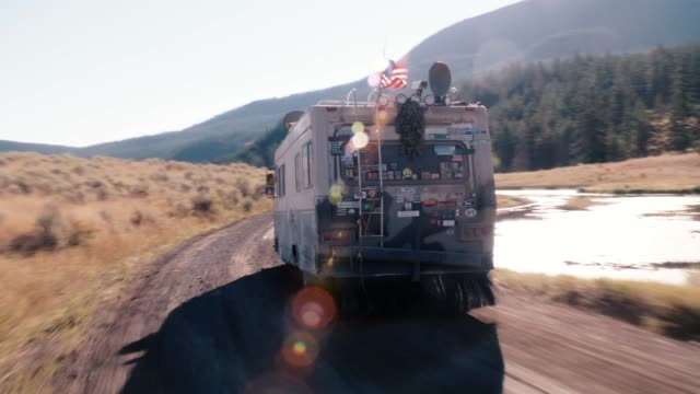tracking shot of rv or recreational vehicle with american flag on roof driving on dirt or country road through wilderness. ponds, pine trees, woods and forest on mountains in bg. sun shining in sky. could be in yellowstone national park. - camper van stock videos & royalty-free footage
