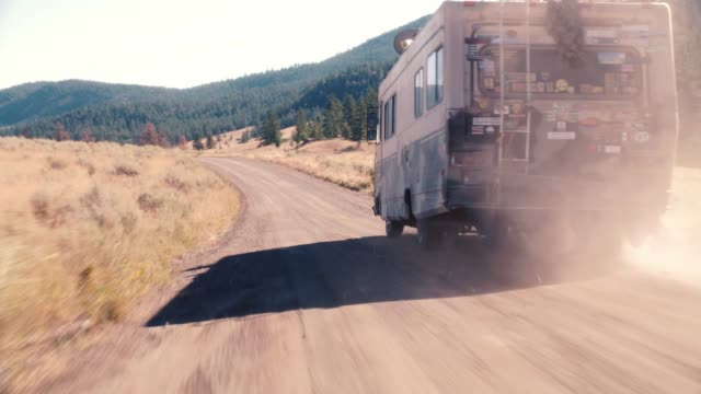 tracking shot of rv or recreational vehicle with american flag on roof driving on dirt or country road through wilderness. trail of dust or smoke. ponds, pine trees, woods and forest on mountains in bg. sun shining in sky. could be in yellowstone national - camper van stock videos & royalty-free footage