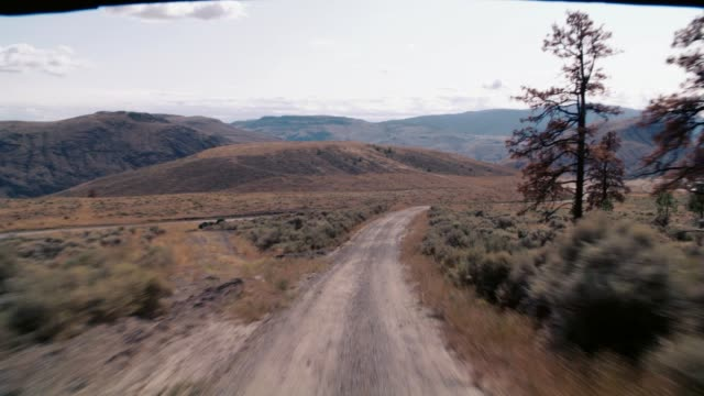 wide angle moving pov of dirt road moving through wilderness area. dry, arid landscape and mountains. industrial buildings or oil tanks on side of road. small cessna airplane sits on runway in bg. - 荒野点の映像素材/bロール