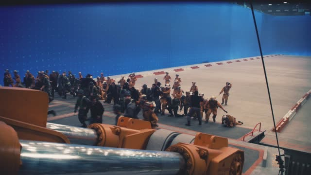 wide angle of crowd of people running and scrambling to get on ramp or loading dock. pistons begin to draw ramp closed. blue screen in bg. - loading screen stock videos & royalty-free footage