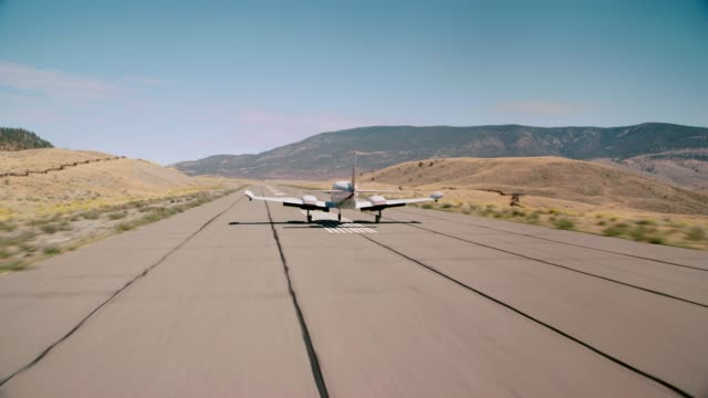 aerial tracking shot of small private propeller airplane landing and taking off from small rural airport runway. wilderness, mountains, hills and fields. could be emergency or crash landing. - propeller aeroplane stock videos & royalty-free footage