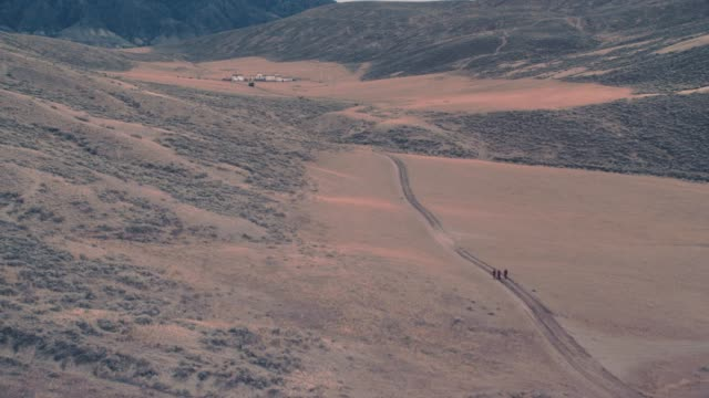 aerial of three tibetan buddhist monks walking on dirt country road in mountains. three army or military trucks in convoy drive past toward military base in bg. could be in china, tibet or nepal. - konvoi stock-videos und b-roll-filmmaterial
