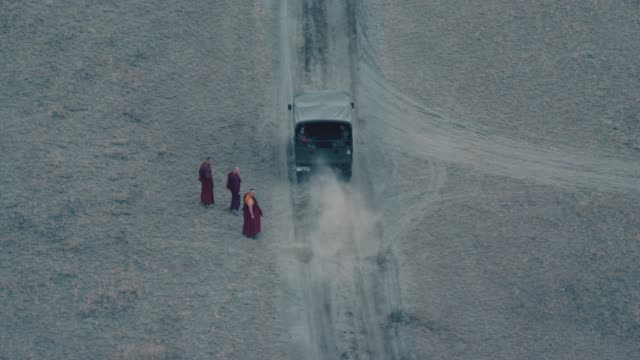 AERIAL OF THREE TIBETAN BUDDHIST MONKS WALKING ON DIRT COUNTRY ROAD IN MOUNTAINS. THREE ARMY OR MILITARY TRUCKS IN CONVOY DRIVE PAST TOWARD MILITARY BASE IN BG. COULD BE IN CHINA, TIBET OR NEPAL.