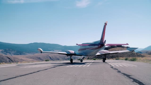 tracking shot of small private propeller airplane moving on runway of rural airport. dry landscape, mountains, hills or countryside. could be for landing or take-off. - hill stock videos & royalty-free footage