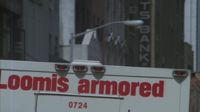 "vídeos de stock, filmes e b-roll de medium angle of top of white armored truck with ""loomis armored"" in red lettering. see top of street lamp and partially blocked bank sign in background. - carro blindado"
