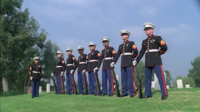 wide angle of an marine officer and seven soldiers standing at attention. military or veterans' cemetery. on command, soldiers turn to left and raise guns to chests. probably part of 21-gun-salute ceremony. military funeral or veteran's memorial service. - us marine corps stock videos & royalty-free footage
