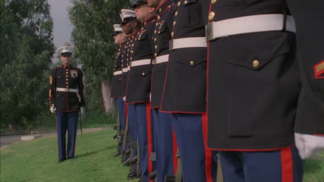 wide angle of an marine officer and seven soldiers standing at attention. military or veterans' cemetery. on command, seven soldiers turn to left, bring guns to chests, and raise them to shoulders three times, presumably conducting a twenty one gun salute - us marine corps stock videos & royalty-free footage