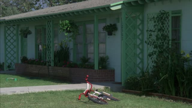 medium angle of one story ranch house with green lattices in front and red tricycle lying on lawn. at end man can be seen exiting from front door. - ranch house stock videos & royalty-free footage