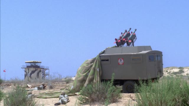 medium angle of surface to air missile launcher and missiles which are launched across and off screen from left to right. air traffic control tower visible in background. middle east. - stapellauf stock-videos und b-roll-filmmaterial