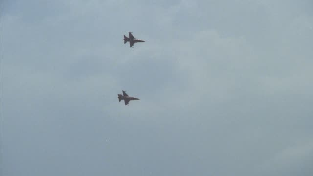 tracking shot of two f-16 fighter jets flying across screen from left to right. - general dynamics f 16 falcon stock videos & royalty-free footage