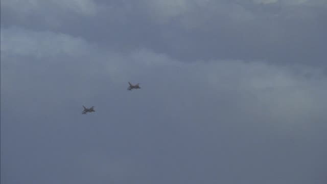 tracking shot of two f-16 fighter jets flying across screen from right to left, perform a left barrel roll and fly off screen to right. neg cut. - mezzo di trasporto aereo video stock e b–roll