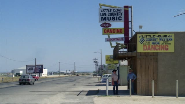 medium angle of desert highway. traffic can be seen passing in both directions. country music bar, nightclub. two men in cowboy hats can be seen standing in front of building. - südwestliche bundesstaaten der usa stock-videos und b-roll-filmmaterial