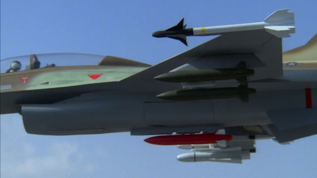 vidéos et rushes de medium angle of side of f-16 fighter jet. two bombs attached to wing are released and fall off bottom of screen. middle east. - bombe