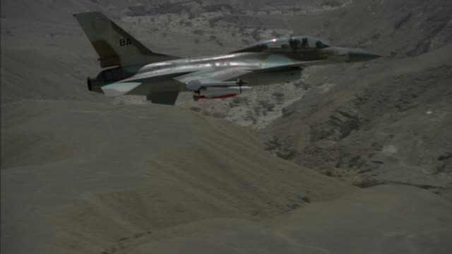 pan left to right of f-16 fighter jet flying across screen from left to right. mountains visible in background. at end jet pulls up and off screen. middle east. - fighter stock videos & royalty-free footage