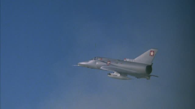 medium angle of saab viggen 37e or kfir military jet fighter model exploding for special effect. strings attached to jet visible. explosions. middle east. - special effect stock videos & royalty-free footage