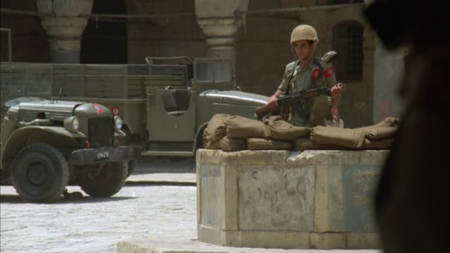 medium angle of soldier in bunker holding rifle. several civilians seen walking in all directions. military jeep can be seen in background. - military land vehicle stock videos & royalty-free footage