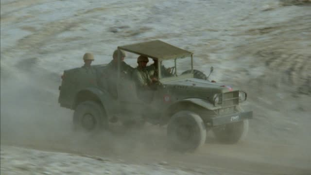 vídeos de stock e filmes b-roll de tracking shot of three green military jeeps driving on desert road. second jeep has four soldiers seated inside. camera pans from side view to front view of second jeep, then zooms out to show all three. camera rotates in counterclockwise motion and stops - jeep