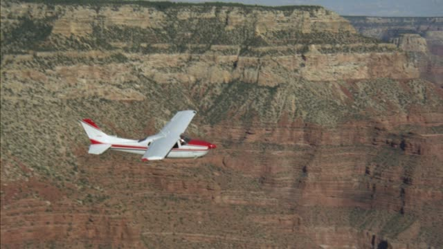 a-a aerial tracking shot of single propeller plane flying over grand canyon. layers of different colored rocks visible in cliff walls. airplane is white and red. - propeller video stock e b–roll