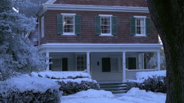 wide angle of a middle class, two story shingle style house with porch. snow covering the trees and bushes.  tree trunk in foreground at right. could be a house or inn. - zweistöckiges wohnhaus stock-videos und b-roll-filmmaterial
