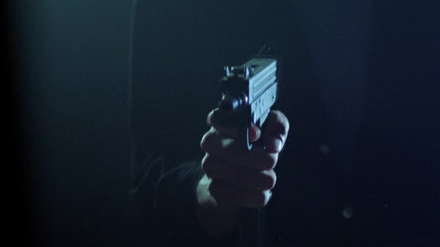close angle of man in black button down long sleeve shirt holding uzi machine gun. he loads gun with clip then cocks it and begins firing. he fires semi-automatically several times until clip is empty. he uncocks gun and removes clip. uzi is lowered to bo - machine gun stock videos & royalty-free footage