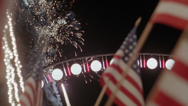 up angle of many fireworks going off. several american flags dominate foreground. pole with red, white, and blue hanging lights in background. probably fourth of july. - fourth of july stock videos & royalty-free footage