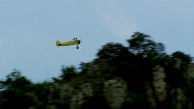 tracking shot of yellow biplane. airplane flies behind mountains or rock outcroppings. blue skies behind plane. - 複葉機点の映像素材/bロール