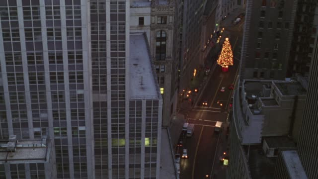 high angle down of brightly lit christmas tree in center of downtown city streets. tall buildings dominate both sides of street. some cars parked on streets. two cars drive through frame. - 1995 stock-videos und b-roll-filmmaterial