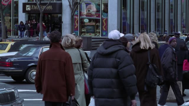 "medium angle of downtown city street intersection. taxis and cars drive through intersection and pedestrians in winter coats walk across street. toy store building in top background with sign that says ""fao schwartz."" - toy store stock videos and b-roll footage"