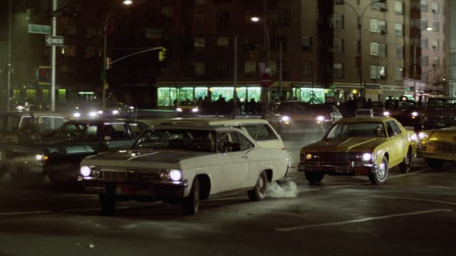 medium angle of intersection in downtown city streets. cars and taxis drive into intersection but stop in a hasty way. drivers run and a mass of people in winter coats come from right in panic fleeing to left in evacuation of disaster. more people come ru - terrified stock videos & royalty-free footage