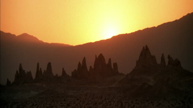 wide angle of establish desert with setting sun. mountains in background and jutting rock spires in foreground. trona pinnacles. - desert stock videos & royalty-free footage