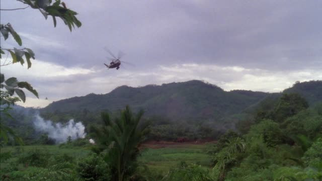 TRACKING SHOT OF MILITARY HELICOPTERS OVER JUNGLE. SEE SMOKE RISING FROM LEFT. TRACKS ONE HELICOPTER LEFT TO EXIT RIGHT, PANS LEFT TO TRACK ANOTHER HELICOPTER FLY LEFT TO EXIT RIGHT. SEE MOUNTAINS IN BACKGROUND AND CLOUDY SKY.