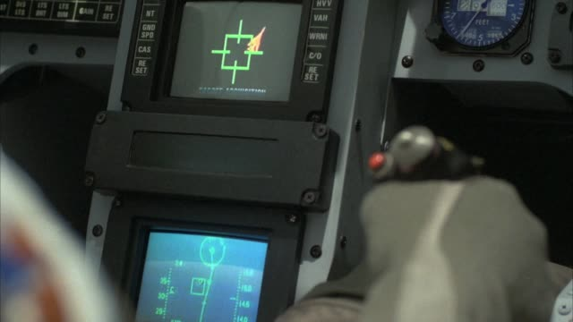 close angle of jet fighter control or throttle stick. see right hand gripping stick. see two jet cockpit screens or monitors, one showing radar, the other showing target lock. see thumb press red button on stick when target is locked on target lock screen - military airplane stock videos & royalty-free footage