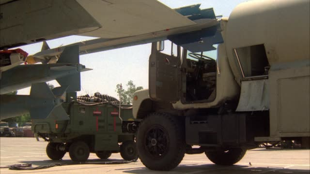 medium angle of underside of jet wing and refuel truck parked on military runway. see armored vehicle in background. flight crew walks up to refuel truck and pulls out fuel hose. then plugs hose into jet body for refueling. middle east. - tanken stock-videos und b-roll-filmmaterial