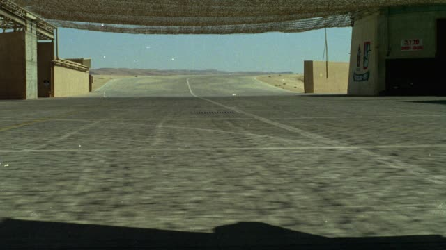 medium angle of desert airplane hangar under desert camouflage netting. see military buildings, maybe base, and runway. middle east. - airplane hangar stock videos & royalty-free footage